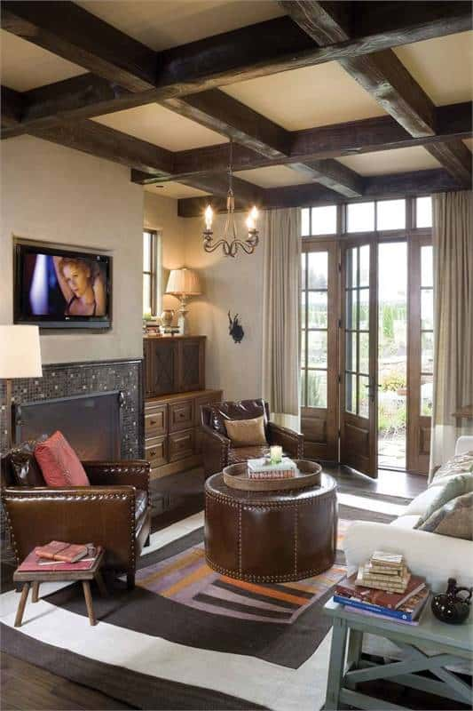 The den offers cozy seats and a wall-mounted TV fixed above the fireplace.