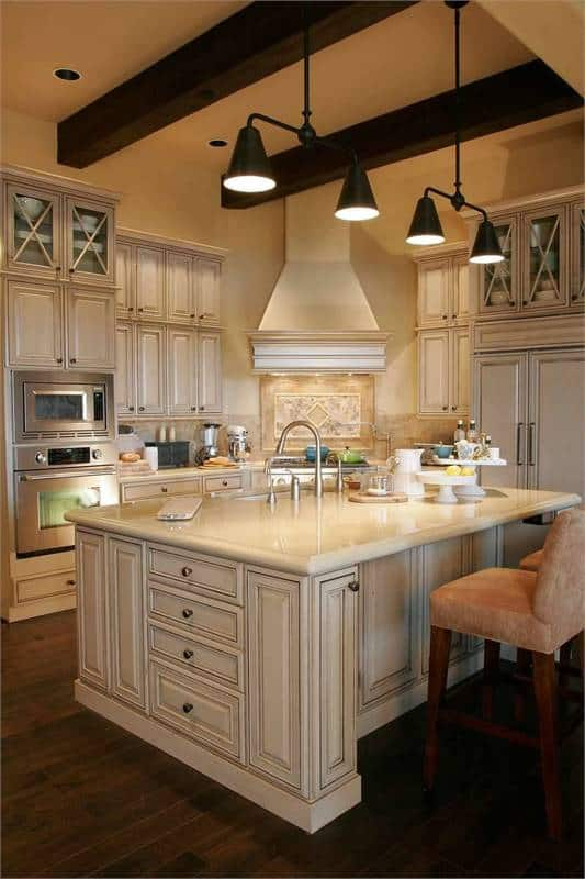 The kitchen features a large center island complemented with cushioned counter chairs and dome pendants hanging from the beamed ceiling.