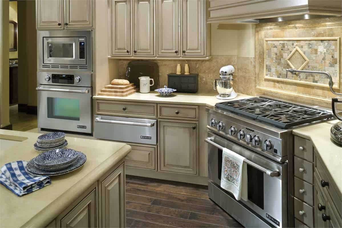 Stainless steel appliances and beige cabinetry that blends in with the marble backsplash complete the kitchen.