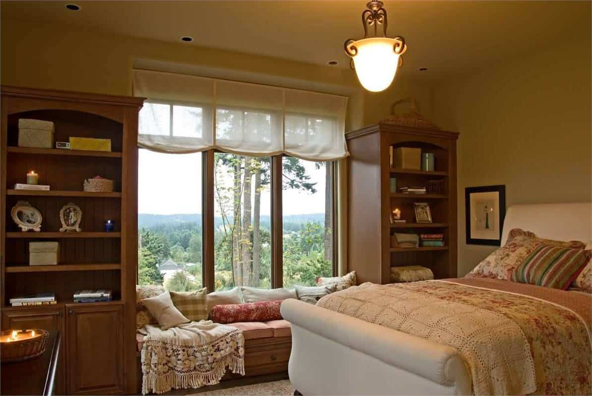 This bedroom has a white upholstered bed and a window seat flanked by wooden cabinets.
