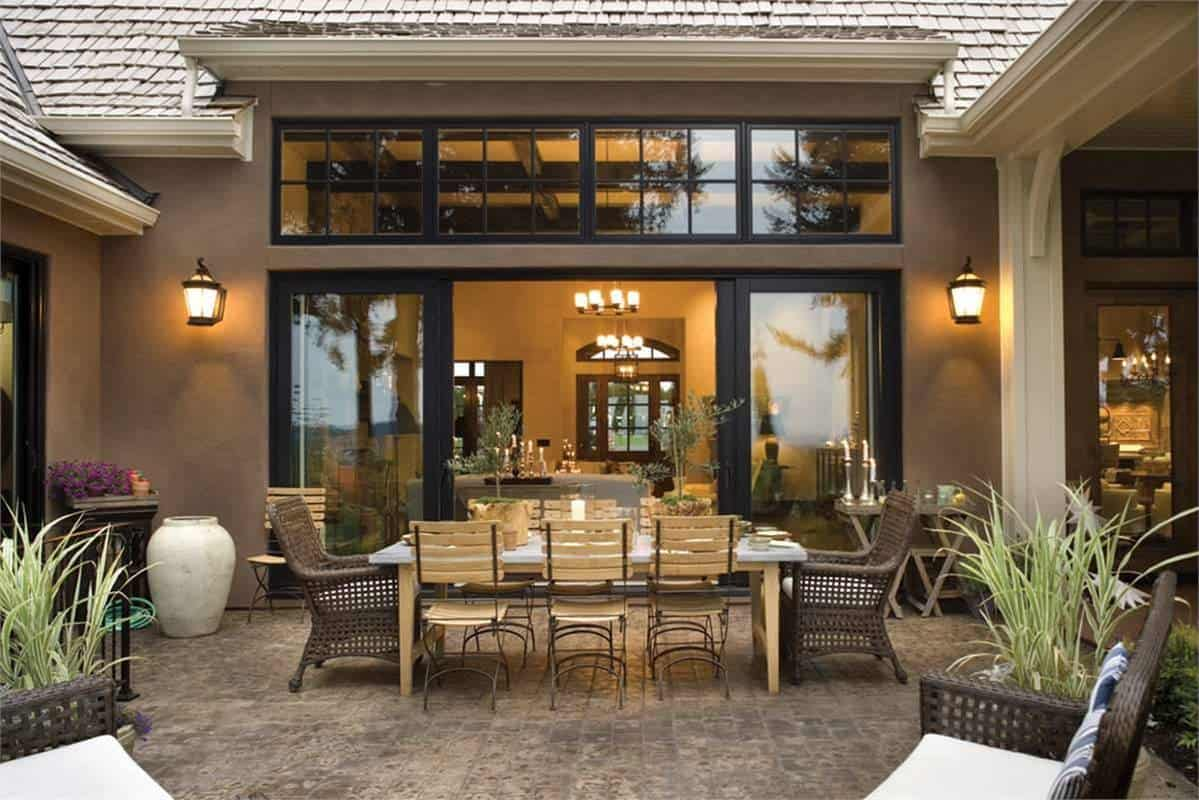 The outdoor living offers wicker chairs and a wooden dining set facing the sliding glass doors of the great room.