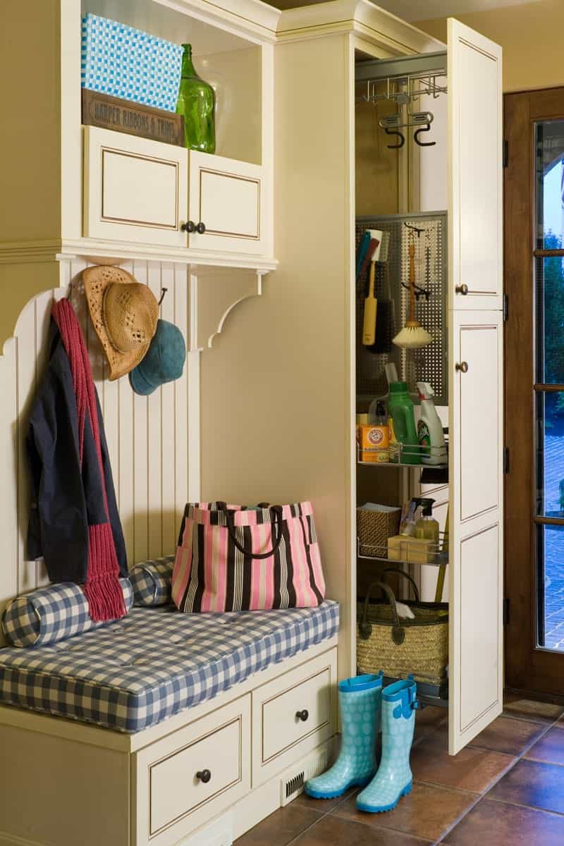 The mudroom offers lots of storage and a built-in seat topped with blue checkered cushion and pillows.