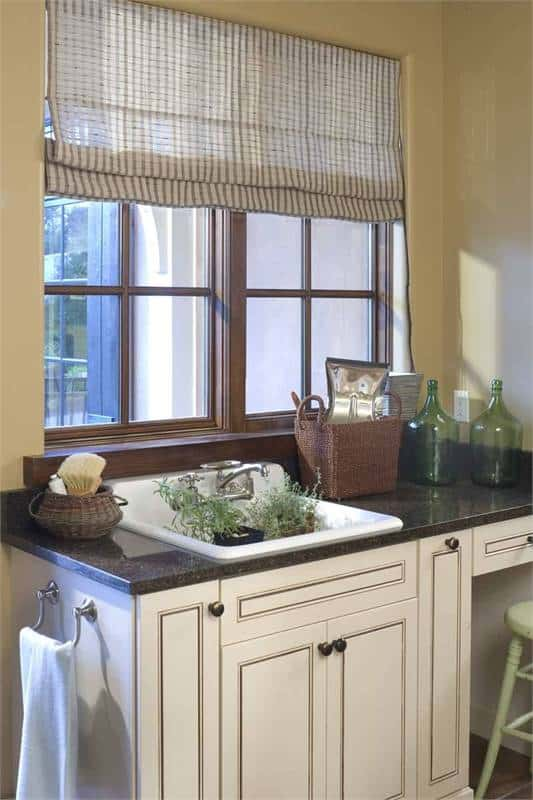 There's also a porcelain sink by the wooden framed windows fitted on the black granite countertop.