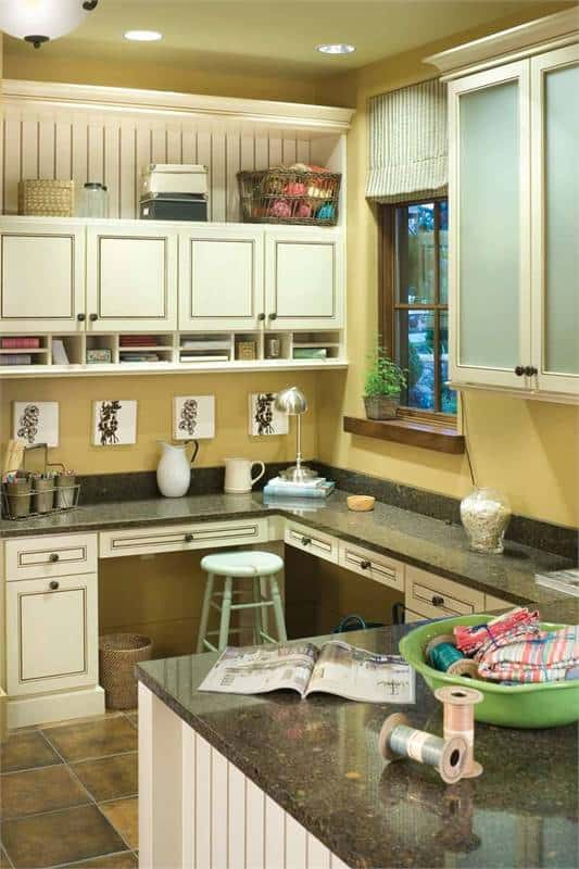 Sewing corner complete with white cabinets and shelves along with granite countertops paired with a green stool.