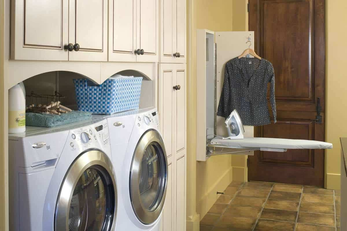 Laundry area with beige cabinets, front load washing machine and dryer, and a built-in ironing board that's a space saver.