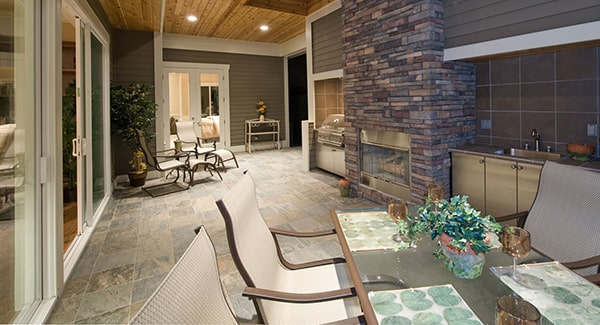 Outdoor kitchen with multiple seats and a brick fireplace flanked by cabinets.