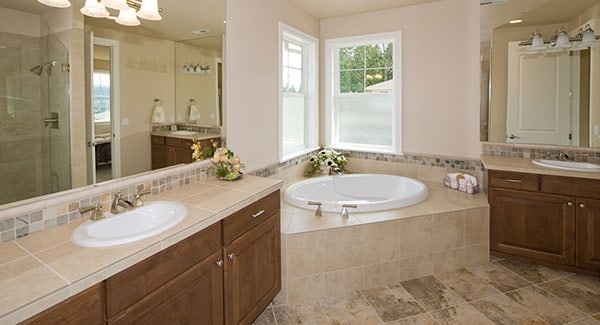 The primary bathroom features a corner tub flanked by wooden sink vanities.