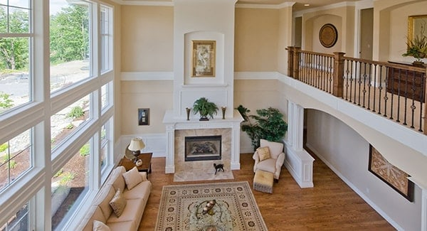 View of the living room from the second floor shows the soaring ceiling and white wainscoted columns that support the balcony.
