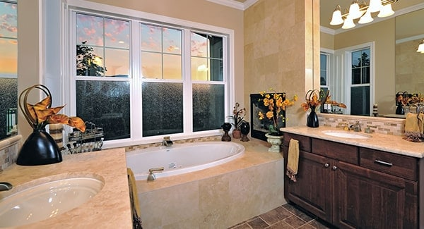 Bathroom with a deep soaking tub and facing sink vanities lit by warm glass sconces.