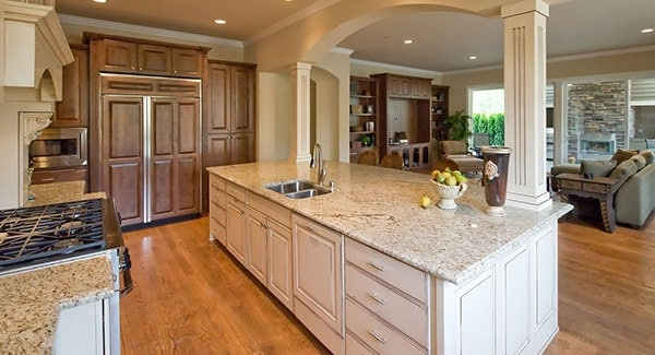 A closer look at the kitchen shows the wooden cabinetry and granite countertops over the white cabinets.