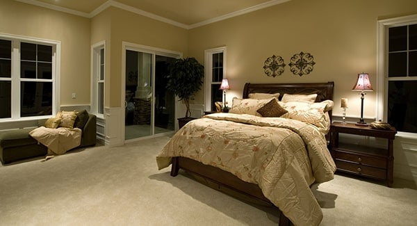 This bedroom is flooded with ambient light coming from the classic table lamps that sit on wooden nightstands.