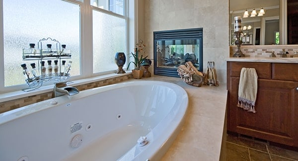 A closer look at this bathroom shows the sink vanity and a drop-in tub complemented by a glass-enclosed fireplace.