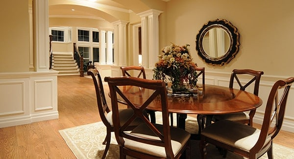 Dining room with polished wooden set and a gorgeous round mirror above the white wainscoting.