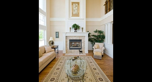The living room features a marble fireplace complemented with a cozy beige lounger.