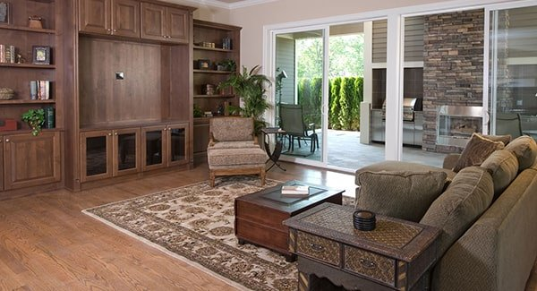Family room with built-ins and cozy seats paired with a dark wood coffee table over a classic rug. Sliding glass doors on the side leads to the outdoor living.