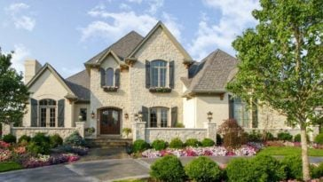 This is a charming two-story Traditional-style home with textured exterior beige walls to pair with its earthy roofs. The house is bordered with low stone walls that match the exteriors complemented by the colorful flowering shrubs of the gorgeous landscaping.