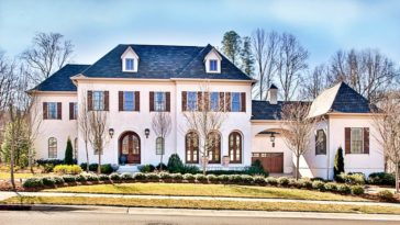 This beautiful two-story Country-style home has arched windows and dormer windows to pair with the beige exterior walls and simple yet elegant landscaping.