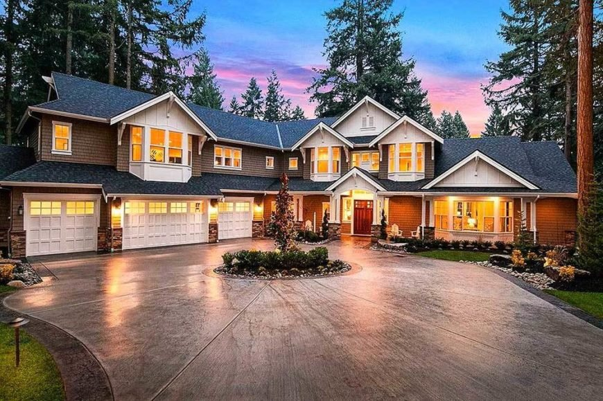 A two-story Craftsman-style home that boasts of a warm and homey quality to its yellow lights coming from windows that bathes the driveway with warmth. There is a circular garden in the middle of the concrete driveway that leads to wide garage doors with wall-mounted lamps.