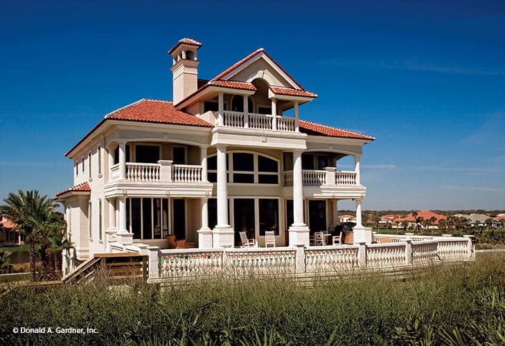 Home's rear view shows the expansive deck and balconies supported by decorative columns.