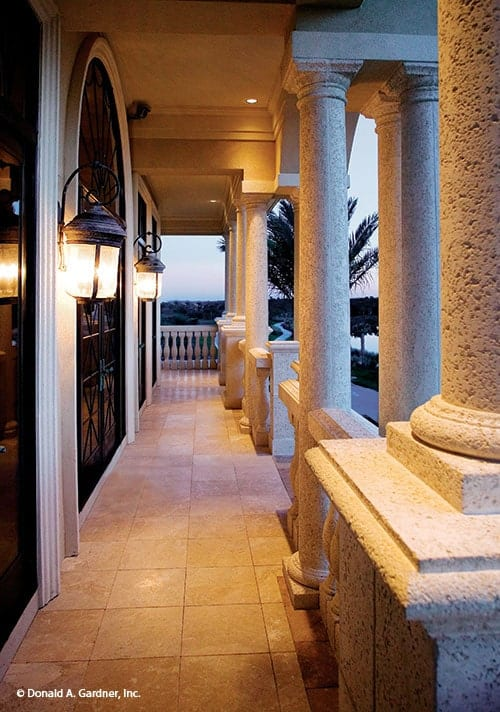 A closer view of the balcony shows the textured columns and marble tiled flooring illuminated by warm recessed lights and sconces.
