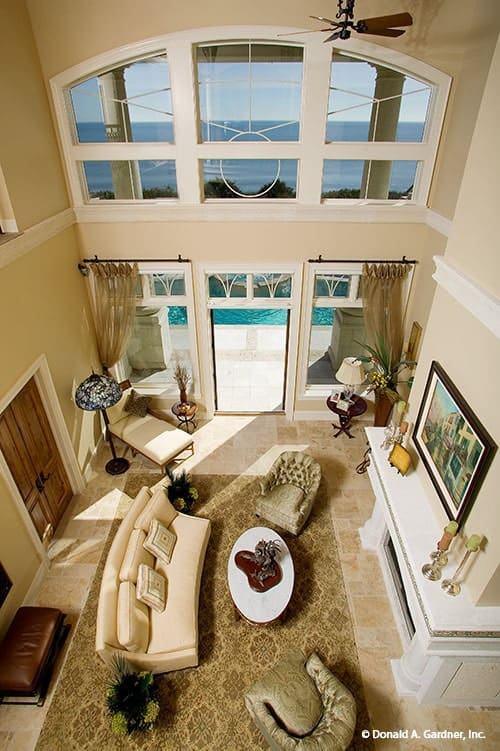 View of the great room from the second-floor balcony showing its soaring ceiling and limestone flooring topped by a classic area rug.