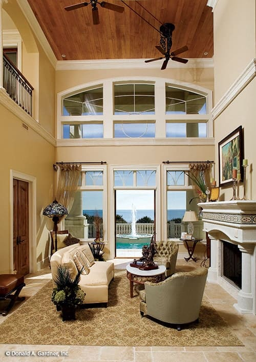 The great room includes an arched transom window and glazed doors leading out to the patio.