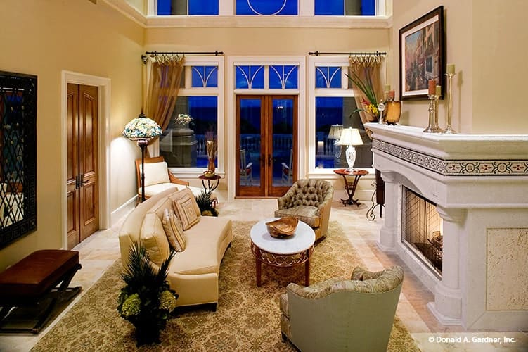 A closer look shows the tufted chairs, round coffee table, and a curved sofa facing the warm fireplace.