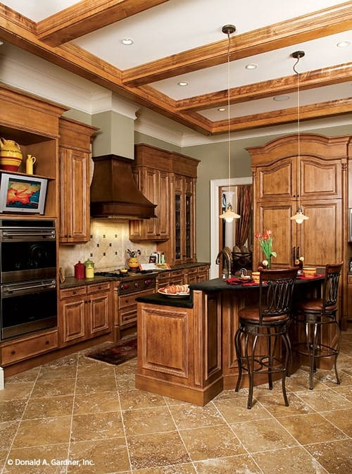Kitchen with wooden cabinetry and a two-tier breakfast island lit by small dome pendants hanging from the beamed ceiling.