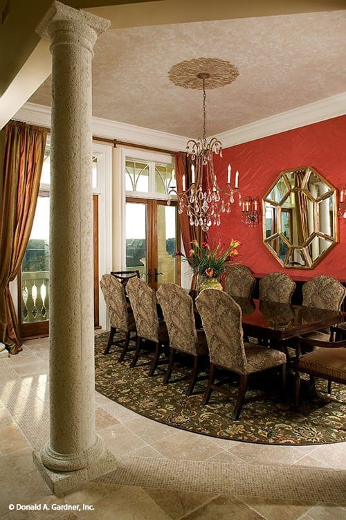 Formal dining room with a crystal chandelier, classy dining set. and an octagonal mirror fixed against the red accent wall.