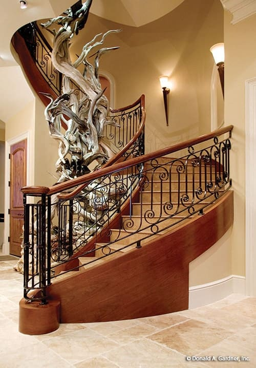 Winding staircase with ornate wrought iron railings wrapping around the intriguing sculpture.
