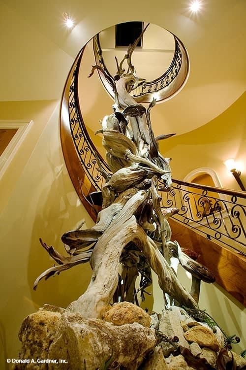 A closer view at the tall driftwood sculpture adorning the winding staircase.