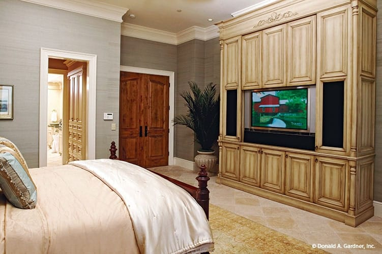This bedroom offers a cozy bed and a TV mounted on the built-in cabinet.