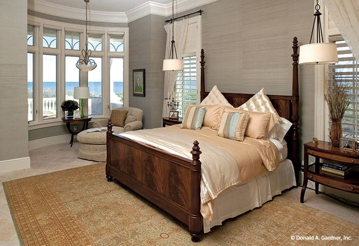 Primary bedroom with a four-poster bed over an antique rug and a sitting area by the bow window with the view of the rear patio.