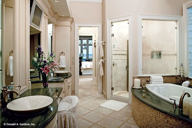 Primary bathroom with a walk-in shower, a deep soaking tub, and dual vanities topped with vessel sinks and black granite countertops.