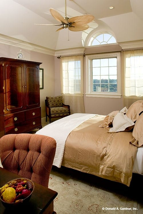 This bedroom has dark wood furniture, white-framed windows and a vaulted ceiling mounted with a fan.