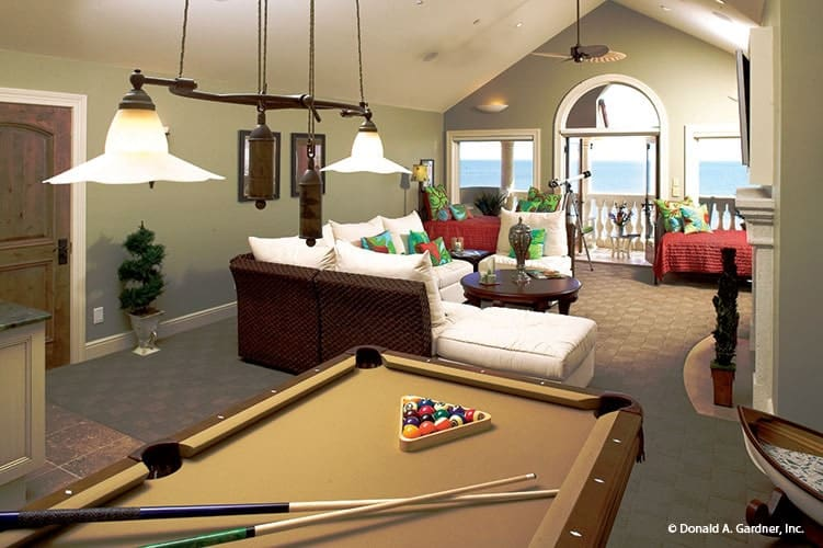 A farther view shows the billiard table under the glass pendant lights.