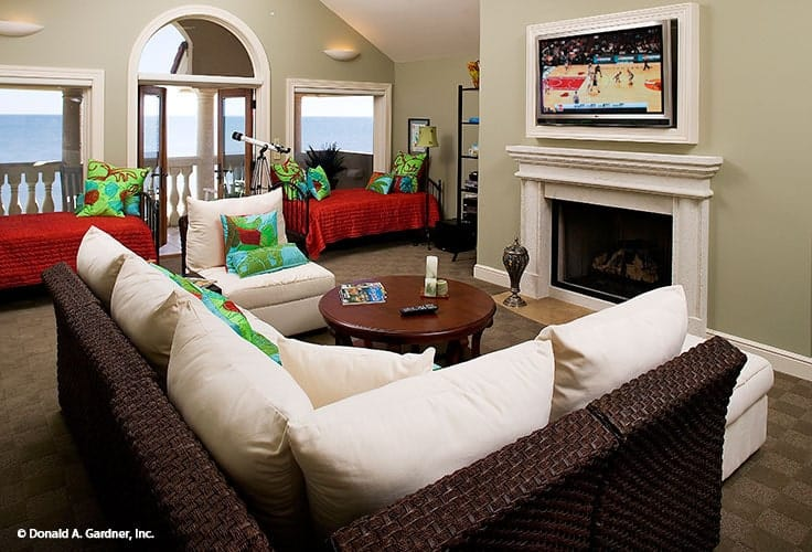 A closer look shows the wicker sofa, a fireplace under the TV, and window seats flanking the french door that leads out to the balcony.