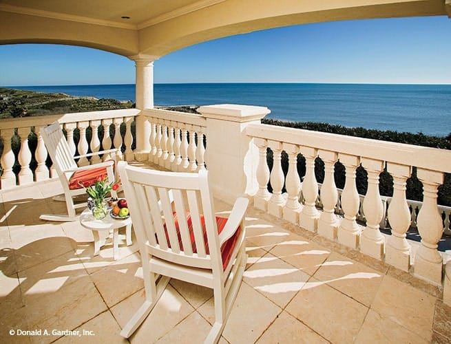 Covered balcony with a small round table and rocking chairs overlooking the magnificent ocean.