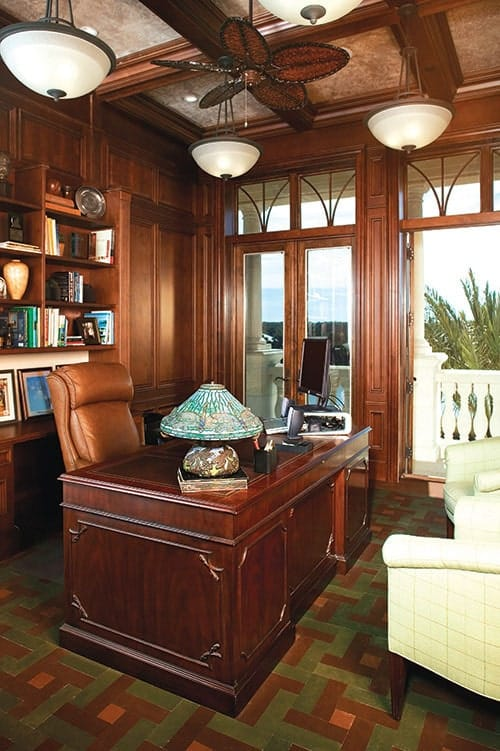 Home office with dark wood desk, wood-paneled walls, and a matching coffered ceiling mounted with fan and glass dome pendants.