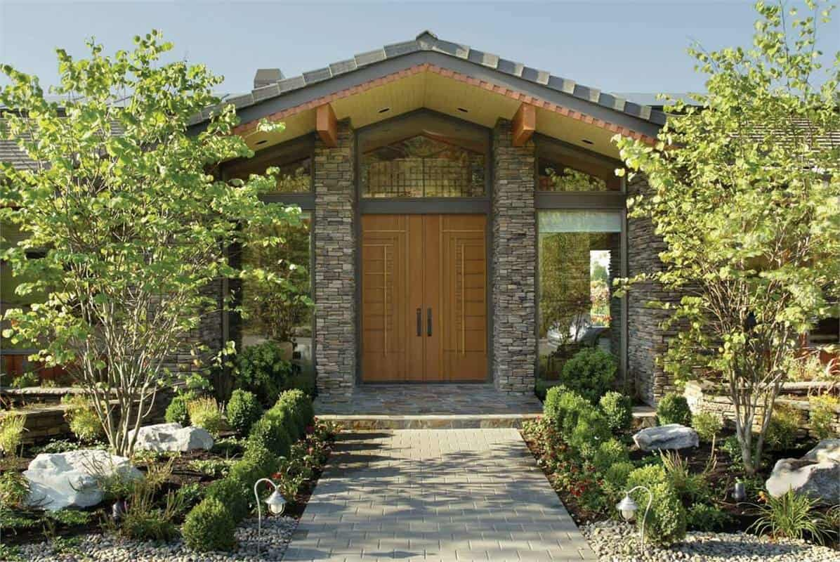 Home's entry with wooden front double door and stone columns supporting the cathedral ceiling.