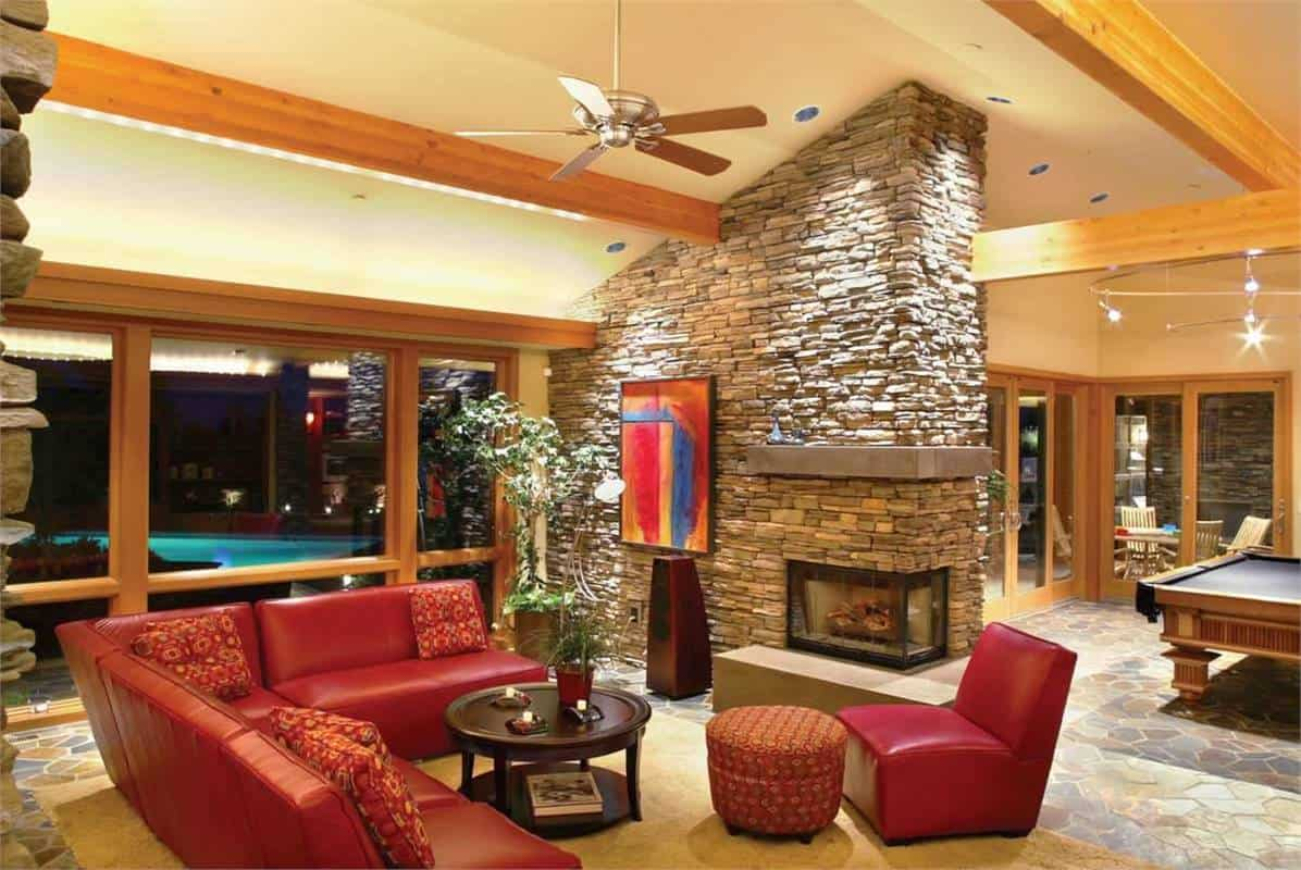 Family room with a dual-sided fireplace, red leather seats, and a wall-mounted TV flanked by built-ins.