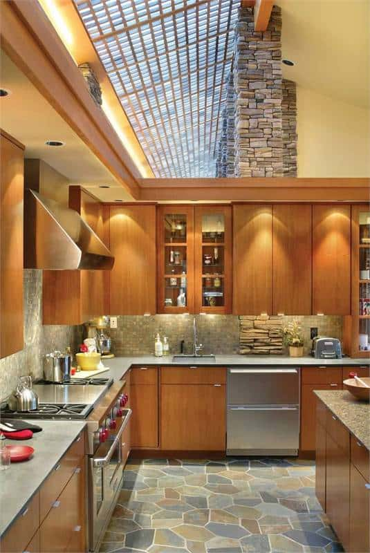 The rich wooden cabinetry is complemented by the mosaic tile backsplash.