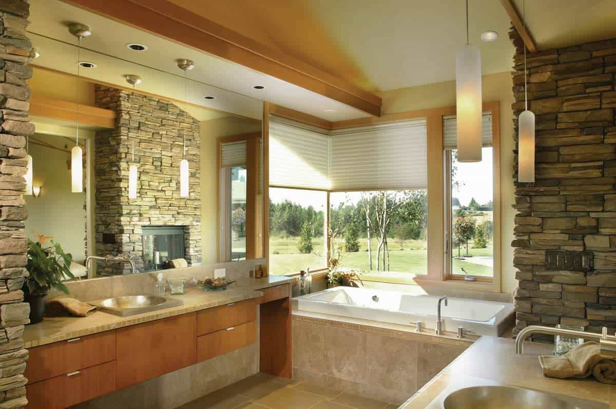 Primary bathroom with facing sink vanities and a deep soaking tub complemented by the stone fireplace.