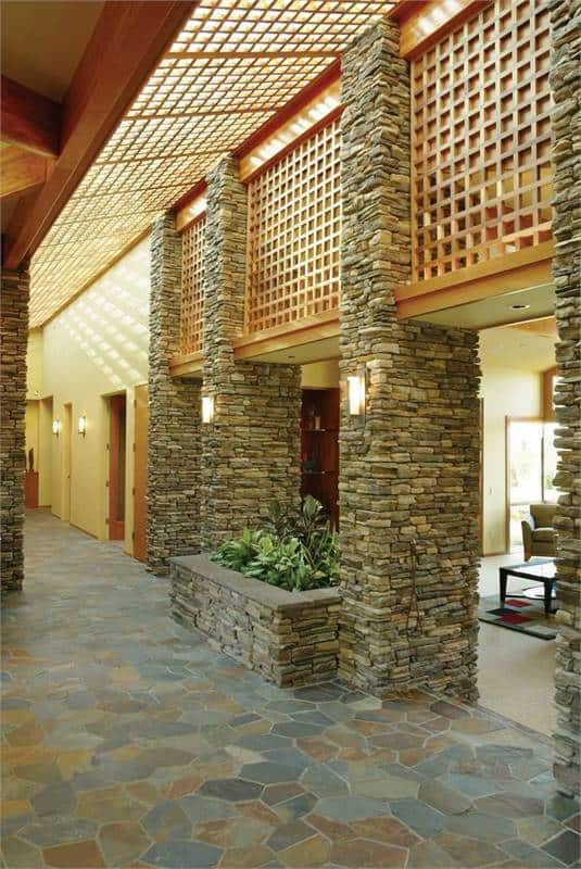 Hallway with a skylight roof system and stone columns mounted with cylindrical sconces.