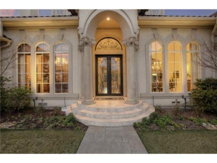 Front french door with framed with an archway that's supported by marble columns.
