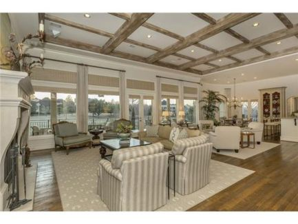 Living room with coffered ceiling and natural hardwood flooring topped by gray patterned rugs.
