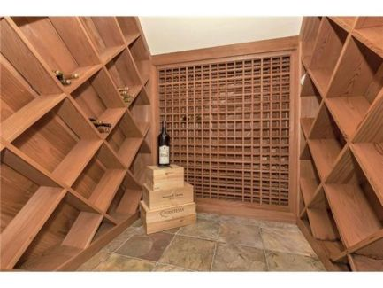 Wine cellar with crisscross shelving and tiered trunks over marble tiled flooring.