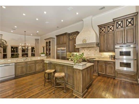 Kitchen with wooden cabinetry and a matching central island blending in with the hardwood flooring.