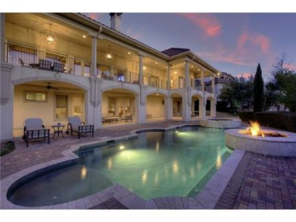 Home's rear view shows the covered lanai and a tranquil pool complemented by a fire pit.
