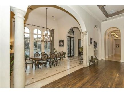 Formal dining room surrounded by archways and windows overlooking the front yard.